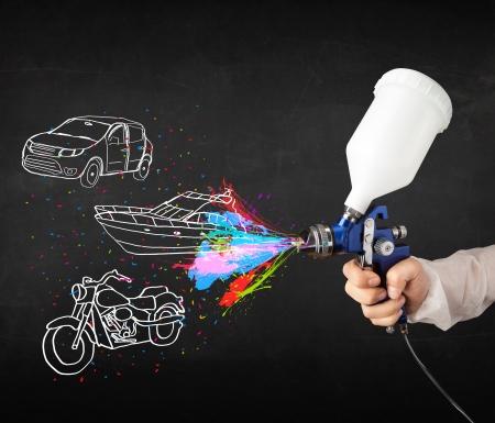 airbrushing: Hombre con la pintura de aerosol del aer�grafo con el coche, el barco y motocicleta dibujo sobre fondo oscuro Foto de archivo