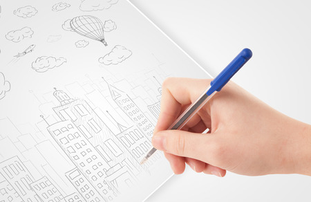 A person drawing sketch of a city with balloons and clouds on a plain paper Stock Photo - 22787985