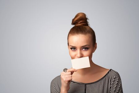 Cute girl holding white card at front of her lips with copy space on gradient background photo