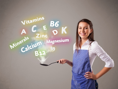 pretty young woman: Pretty young woman cooking vitamins and minerals