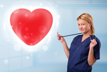 Pretty young nurse healing a red heart photo