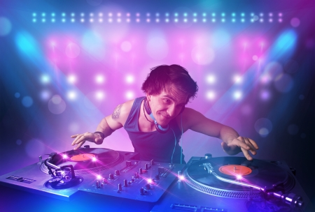 Young disc jockey mixing music on turntables on stage with lights and stroboscopes photo