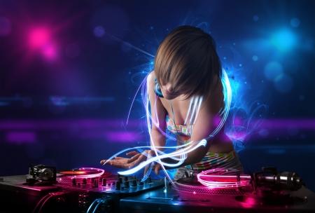 tocando musica: Hermosa disc jockey tocando m�sica con efectos de luz electro y luces