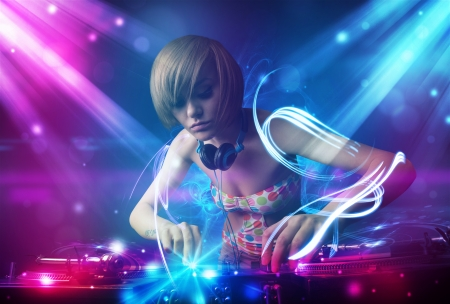 electronic: Energetic Dj girl mixing music with powerful light effects Stock Photo