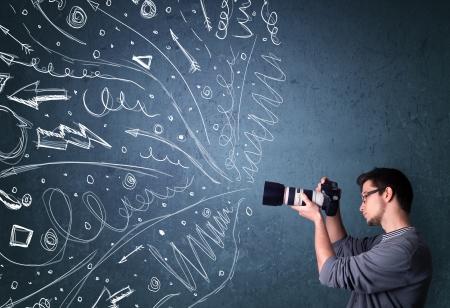 Fotograaf jongen fotograferen terwijl energieke hand getekende lijnen en doodles komen uit de camera Stockfoto