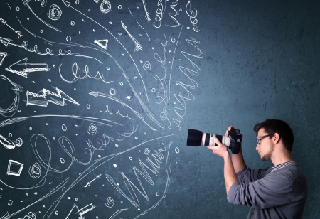 taking video: Photographer boy shooting images while energetic hand drawn lines and doodles come out of the camera