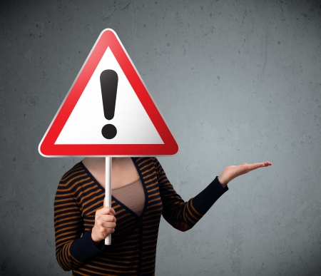 Young woman holding a red traffic triangle warning sign in front of her head Stock Photo - 22962908
