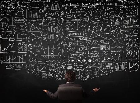analyse: Jeune homme d'affaires assis dans une chaise de bureau devant un tableau noir avec des graphiques et des signes dessin�s