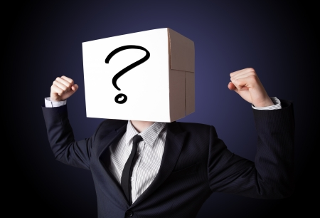 Businessman standing and gesturing with a cardboard box on his head with question mark photo