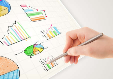 Business person drawing colorful graphs and icons on plain paper photo