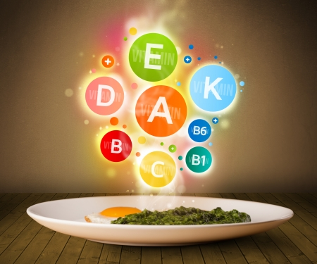 Food plate with delicious meal and healthy colorful vitamin symbols  photo