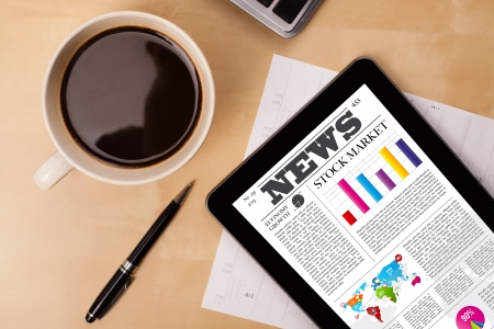 stock news: Workplace with tablet pc showing latest news and a cup of coffee on a wooden work table close-up Stock Photo