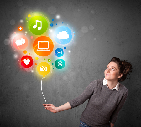 gesticulation: Pretty young woman holding colorful social media icons balloon Stock Photo