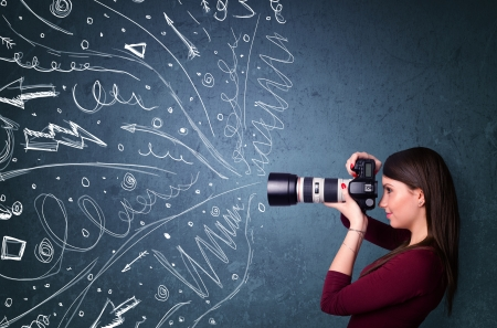 Photographer girl shooting images while energetic hand drawn lines and doodles come out of the camera Stock Photo