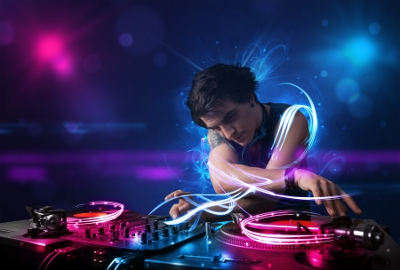 tocando musica: Disc jockey joven que juega m�sica con efectos de luz electro y luces