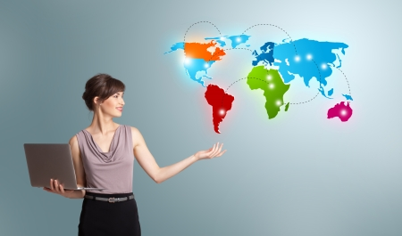 intercontinental: Beautiful young woman holding a laptop and presenting colorful world map