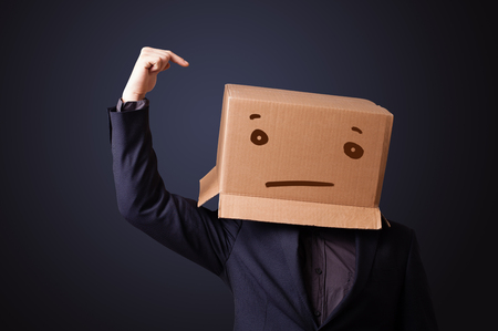 straight man: Young man standing and gesturing with a cardboard box on his head with straight face Stock Photo