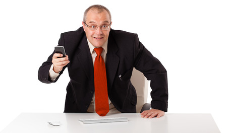 businessman sitting at desk and holding a mobilephone with copys pace, isolated on white photo