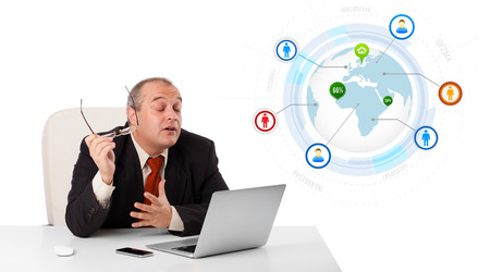 businessman sitting at desk and looking laptop with globe and social icons, isolated on white photo