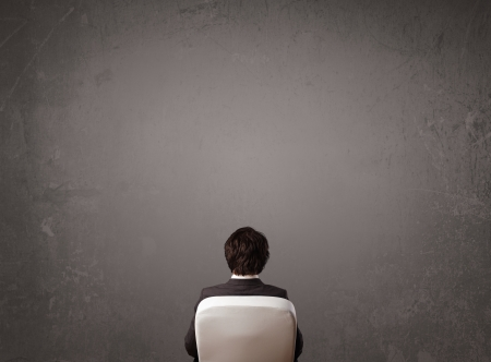 Young businessman sitting in office chair in front of a wall with empty space photo