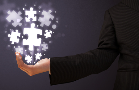 Businessman holding shining puzzle pieces in his hand photo