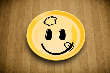 Happy smiley cartoon face on colorful dish plate and grungy background