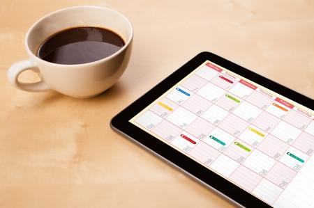 Poste de travail avec tablette pc montrant calendrier et une tasse de café sur une table de travail en bois close-up Banque d'images - 23160696