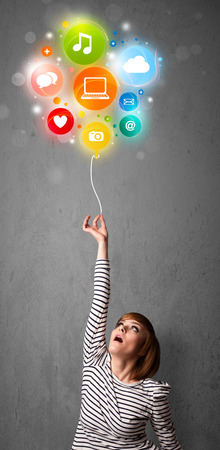 Pretty young woman holding colorful social media icons balloon photo