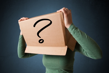 Young lady standing and gesturing with a cardboard box on her head with question mark photo