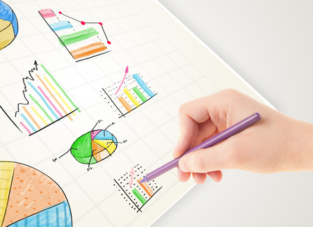 Business person drawing colorful graphs and icons on plain paper Stock Photo