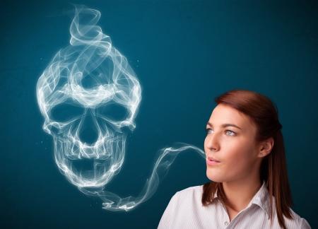 Pretty young woman smoking dangerous cigarette with toxic skull smoke Stock Photo - 23509490