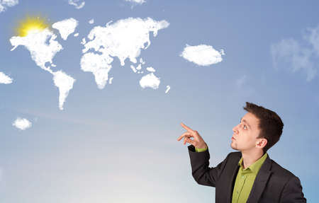 Businessman looking at world clouds and sun on blue sky photo