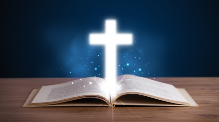 bible story: Open holy bible with glowing cross in the middle on wooden deck Stock Photo
