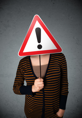 Young woman holding a red traffic triangle warning sign in front of her head Stock Photo - 23484094