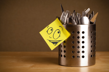 Drawn smiley face on a post-it note sticked on a cutlery case Stock Photo - 23736743