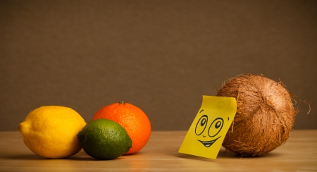 reacting: Coconut with sticky post-it note reacting on citrus fruits Stock Photo