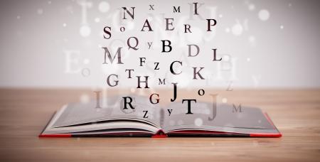 diccionarios: Libro abierto con las letras que vuelan en el fondo de hormig�n Foto de archivo