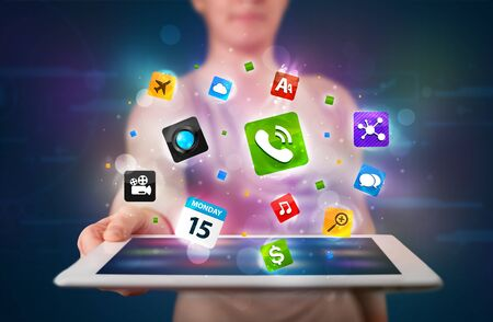 Young lady holding a tablet with modern colorful apps and icons photo