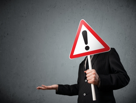 Businessman holding a red traffic triangle warning sign in front of his head Stock Photo - 23737091