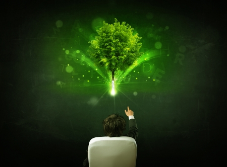 Young businessman sitting in office chair with a glowing tree and letters above his head photo