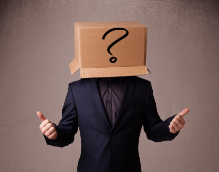 Young man standing and gesturing with a cardboard box on his head with question mark photo