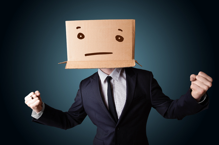 gesticulation: Businessman standing and gesturing with a cardboard box on his head with straight face