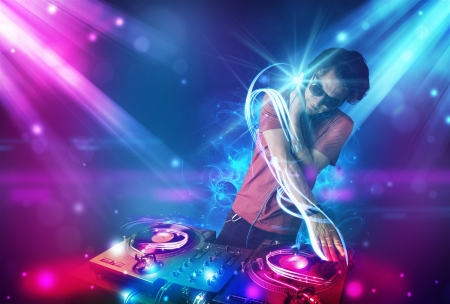 Young energetic Dj mixing music with powerful light effects photo