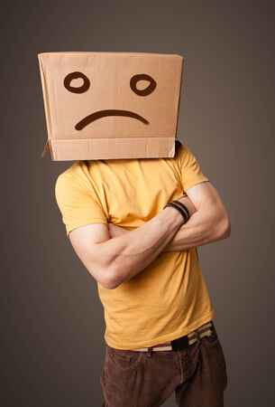 sad face: Young man standing with a brown cardboard box on his head with sad face Stock Photo