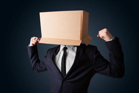 masquerader: Businessman standing and gesturing with a cardboard box on his head Stock Photo