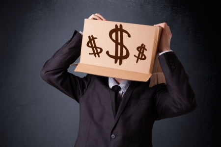Young man standing and gesturing with a cardboard box on his head with dollar signs photo