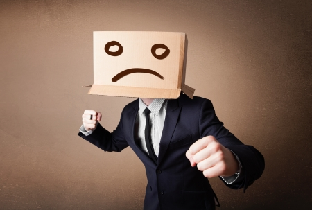 Businessman standing and gesturing with a cardboard box on his head with sad face photo