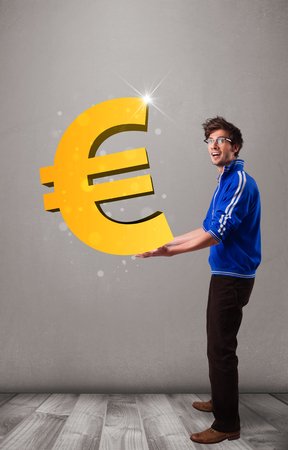 Good-looking young boy holding a big 3d gold euro sign photo