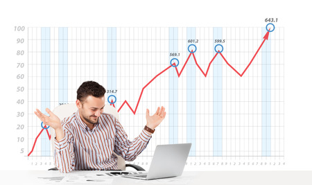 Young businessman calculating stock market with rising graph in the background photo
