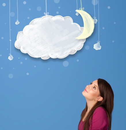 Young girl looking at cartoon night clouds with moon hanging down photo